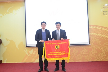 Ông Bùi Chí Hiếu - Bí thư Đoàn thanh niên Bộ Xây dựng tặng cờ thi đua cho Viện KTQG