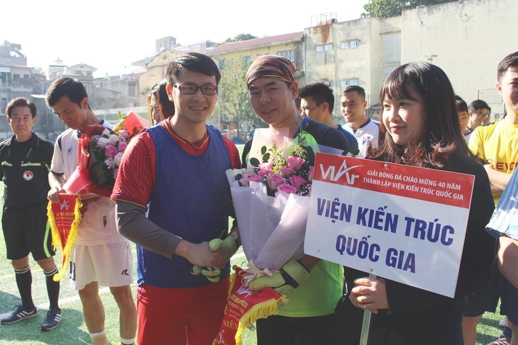Ông Bùi Chí Hiếu - Ủy viên Ban Chấp hành Đảng bộ Bộ Xây dựng, Bí thư Đoàn Thanh niên Bộ Xây dựng tặng hoa và trao cờ lưu niệm cho đội bóng Viện Kiến trúc Quốc gia.